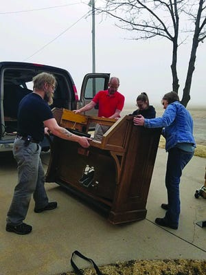 Members of the Trinity Community Church congregation help load their 1939 organ into a moving van so that it may be sent off for repairs on a foggy morning earlier this month in Hudson. They hope it will be back, good as new, by Easter Sunday, April 12, 2020.