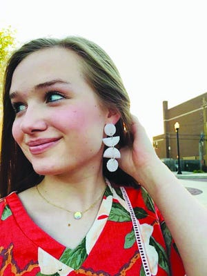 Kailey Hamm of Pratt models one variety of clay earrings she created. She had time during school quarantine days to create many types of earrings and now has a small business selling her crafts at N'Cahoots Coffee and Shoppe in Pratt.