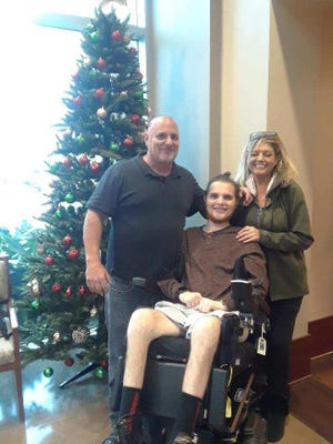 Justin Amico's dad, Roy, with his mom, Kelley Howell, and Justin just before Christmas. Roy Amico has taken over the care of his son after Kelley died last month.