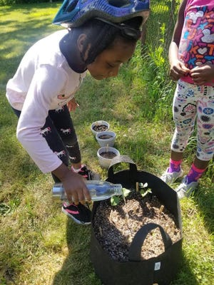 Participants water their container gardens made through Roc Kids Grow.
