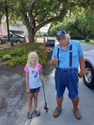 John Simensen helps a young visitor from Maryland learn to fish with a brand new fishing rod.