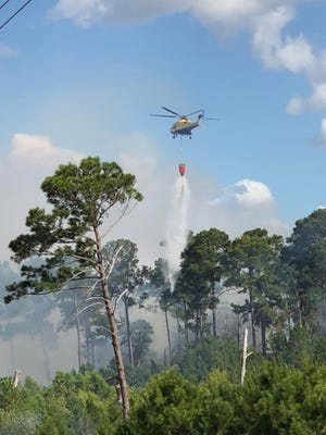 A STAR Flight helicopter dropped water on a 27-acre wildfire in Bastrop State Park torched Monday. State and federal firefighters were continuing fire containment work Tuesday as they let the fire burn itself out. Smoke is expected to continue from the fire for several days, officials said.