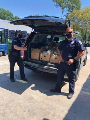 """Fort Smith police officers Robyn Shoptaw, left, and Ryan Arritt assist Antioch for Youth & Family in the nonprofit's """"Drop and Knock"""" food delivery program on Tuesday, Aug. 25, 2020."""