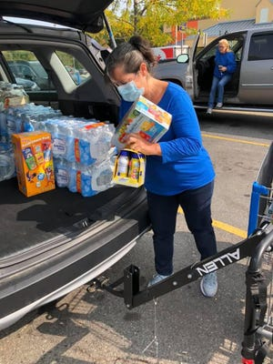 "Stacy Bergeron, founder of Boxes of Love for the Homeless, loads items purchased for a ""huge"" day of caring to support houseless people and others in need outside the Rochester Community Center on Saturday, Sept. 19. The nonprofit and volunteers from throughout the region will provide food, clothing, bicycles, haircuts and more during the event."