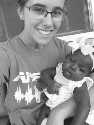 New Franklin resident Nina Wilson cares for an infant as part of performing missionary work in Haiti.