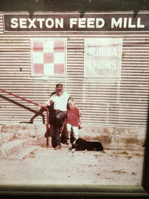 Ronald Sexton and one of his grandsons, Taylor Sexton, are pictured in front of the former Sexton Feed Mill building. The photo was taken more than 20 years ago.