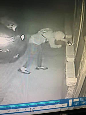 One of the burglars wears distinctive shoes that are light colored on top and dark colored on the bottom. There is also a black, vertical stripe on the back with a loop at the top