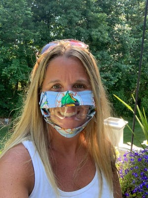 A day care owner models one of the ClearMasks coverings designed by Raynham resident Jodee Viola for the coronavirus.