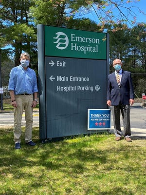 Steve Rowe of Sudbury, left, is seen with Karl Kussin, VP of Development at Emerson Hospital . Rowe's lawn sign fundraiser for Emerson Hospital raised over $3,000 for its COVID-19 fund.