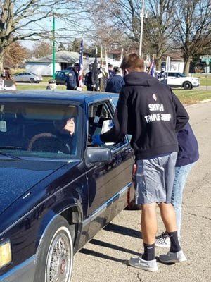 Wethersfield Student Council members Ben Smith and Aimee Moore present a plaque made by the high school woodworking class and a goody bag to a veteran as he passes by during the Veterans Day Drive-by Parade held Wednesday afternoon.