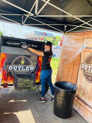 A staff member at Outlaw Roasted Corn places food in the roaster. The stand will be open for the next few weekends from 12-8 p.m. Fridays-Sundays.