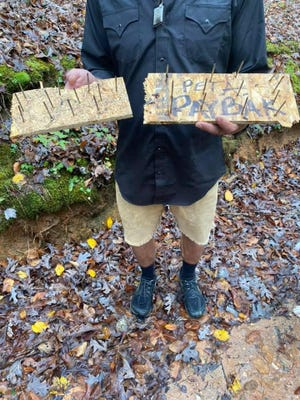 "Tyler Mayo of Etowah holds two ""nail traps,"" boards hammered with nails that were hidden Oct. 24 on a trail in the Mills River area of Pisgah National Forest."