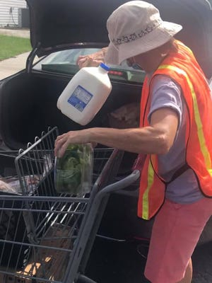A volunteer loads milk into a car last Wednesday. There will be no food distribution this week.