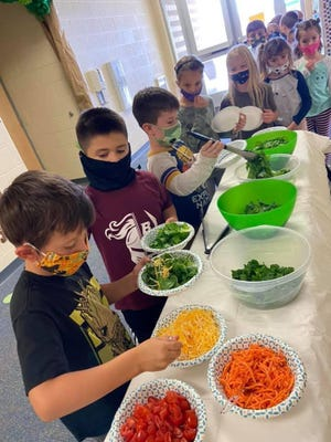 Students in Morgan Starkweather's second grade class enjoy lettuce grown in their classroom.