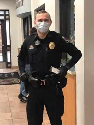 A Holland Police Department police officer wears a face mask to prevent the spread of COVID-19 while taking 911 calls. All police agencies in the Holland area are still responding to calls, including calls for domestic violence and child abuse.