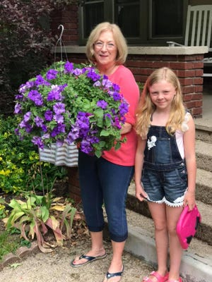 Julie Stratos and her granddaughter, Zoey, enjoy the hanging flower basket that was given to her from the club to help her celebrate her award.