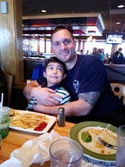 Fond du Lac City Fire Department paramedic Jack Prall hugs Dyland Sanchez during lunch at Applebees last month.