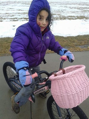 Marina Avila, 6, is pictured with her new bike, Pink Thunder.