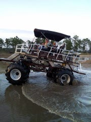 Dixie Sharpe of Immokalee drives out of a mud pit at the Redneck Yacht Club. Sharpe and his wife, Mona, often give rides on their custom-built buggy, Buck Daddy.