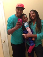 Delvon Roe, left, and Lykendra Johnson pose with their 3-year-old daughter Destinie in December 2014. Roe played men's basketball for MSU, while Johnson played women's basketball before embarking on a professional career overseas.