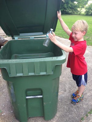Braedon Collins throws out a plastic water bottle, which now will be recycled without having to separate it from the other trash.