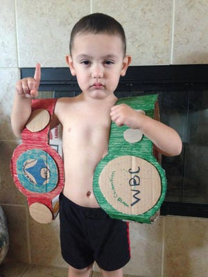 Three-year-old Julian Rios poses with two home-made boxing championship belts.