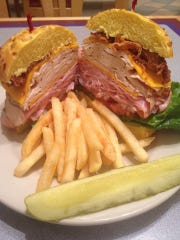 The Papa's Club sandwich at Miracle Mile Deli comes with white meat turkey breast and honey cured ham, crisp bacon, aged cheddar cheese, lettuce, tomato, onion and mayo.