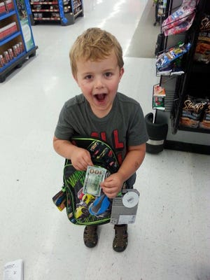 Jackson Elvin reacts to finding a $100 bill signed by Benny in a Hot Wheels backpack that he and his mom, Krissy Elvin, purchased July 28 at the Walmart on Commercial Street SE.