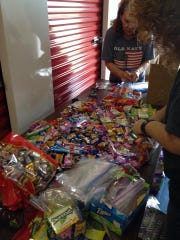 Volunteers pack candy and other goodies for deployed troops at a recent packing for the local Operation Support Our Troops chapter.