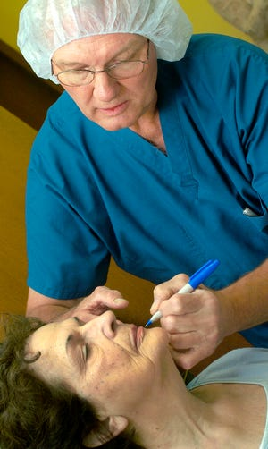 Dr. Paul Benien uses a marker to plot lines where contour thread will run through Effie Jones' face before she is taken into surgery room in 2005. Benien, a former OU football player, died Wednesday at 80. [Oklahoman archives]