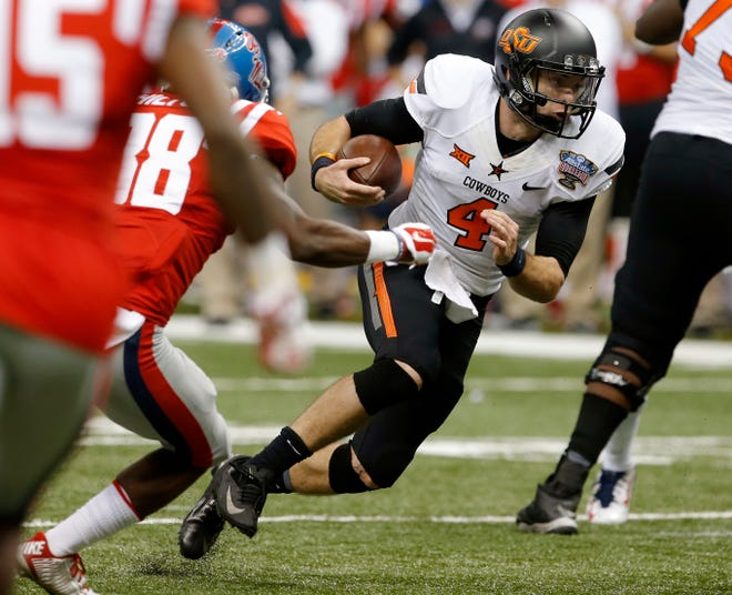 Oklahoma State's J.W. Walsh (4) scrambles during the Allstate Sugar Bowl against the Ole Miss Rebels at the Mercedes-Benz Superdome in New Orleans on Jan. 1, 2016. [Bryan Terry/The Oklahoman]