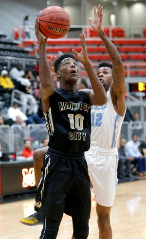 Midwest City's Kevin Overton goes to the basket past Lawton Eisenhower's Mark Berry during the Mustang Holiday Classic basketball tournament championship game between Midwest City and Eisenhower in Mustang, Okla. Saturday, Dec. 29, 2018. Photo by Bryan Terry, The Oklahoman