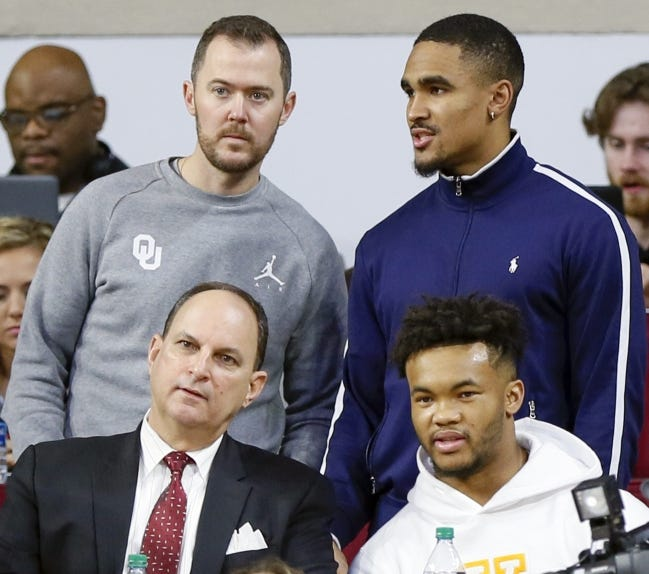 Former OU quarterback Jalen Hurts, upper right, talks to football coach Lincoln Riley as they stand behind athletic director Joe Castiglione and Heisman-winning quarterback Kyler Murray during a 2019 men's college basketball game against Texas in Norman. [Nate Billings/The Oklahoman]