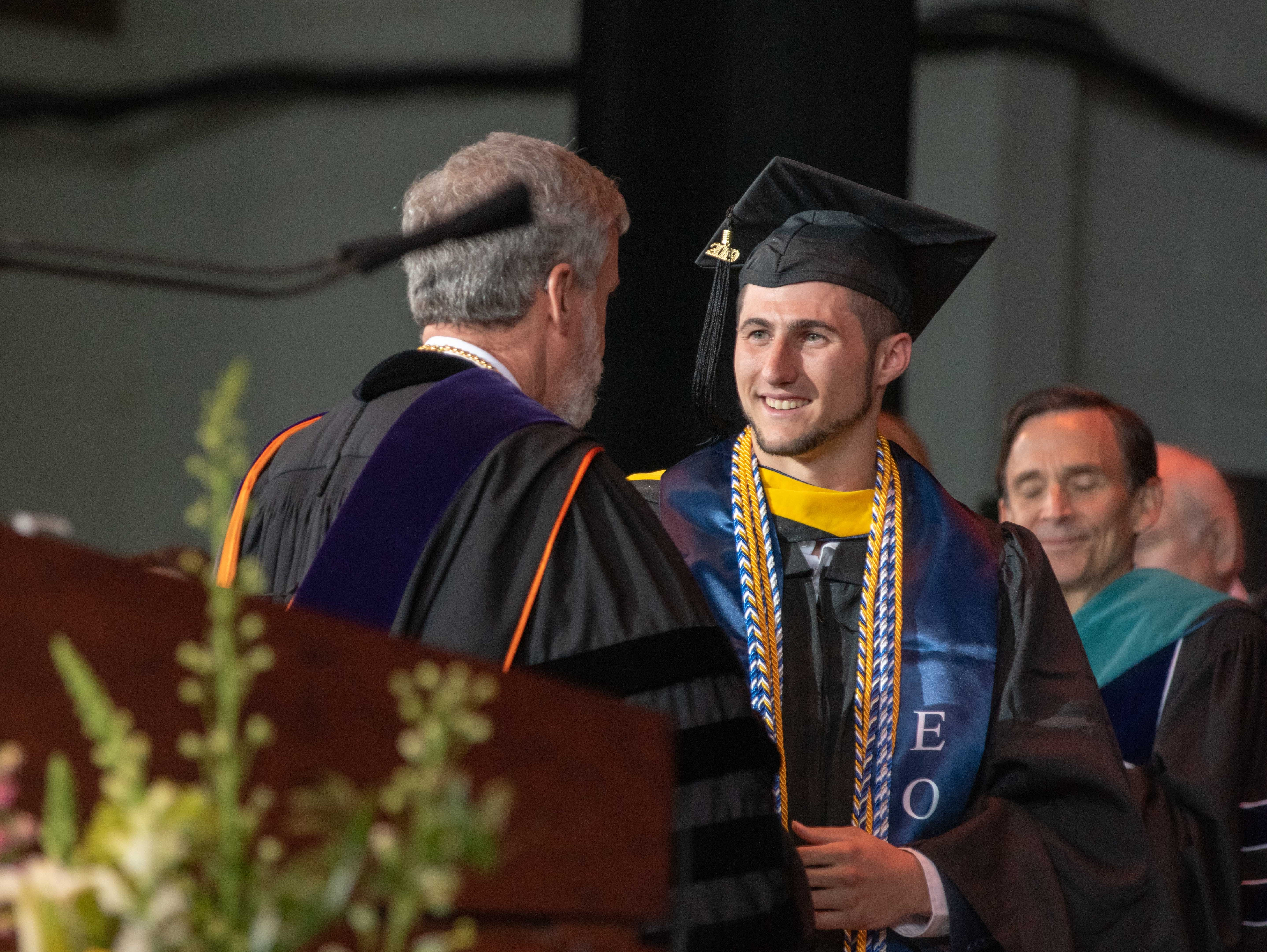 Outgoing Monmouth University president  Grey J. Dimenna introduces Nicholas A. Plodwick, class president, at the Monmouth University undergraduate commencement for the class of 2019 at PNC Bank Arts Center, Holmdel, on May 15, 2019.