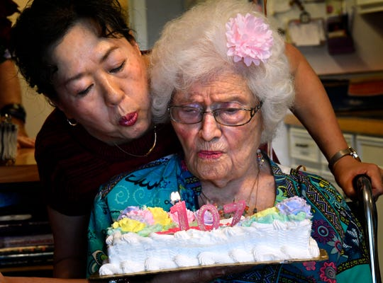 "Gladys Henson gets an assist from Sue Gibson in blowing out candles on the cake celebrating her 107th birthday Wednesday. On the cake, wording encouraged the birthday girl to ""Stay Fabulous."""