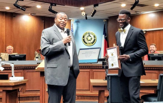 Mayor Anthony Williams smiles as he presents incoming Place 6 Abilene City Council member Travis Craver a plaque during his swearing-in ceremony Wednesday.
