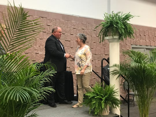 Abilene ISD board Vice President Daryl Zeller shakes the hand of Louwanna Winland after she was recognized for 20 years of service to the school district during a ceremony at the Abilene Convention Center Wednesday. Winland also was recognized as one of 71 district employees retiring at the end of this year.