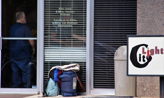 Backpacks and other items are left at the door of City Light Community Ministries during a lunch serving Wednesday. Signage indicates other activities, including Sunday Bible study.