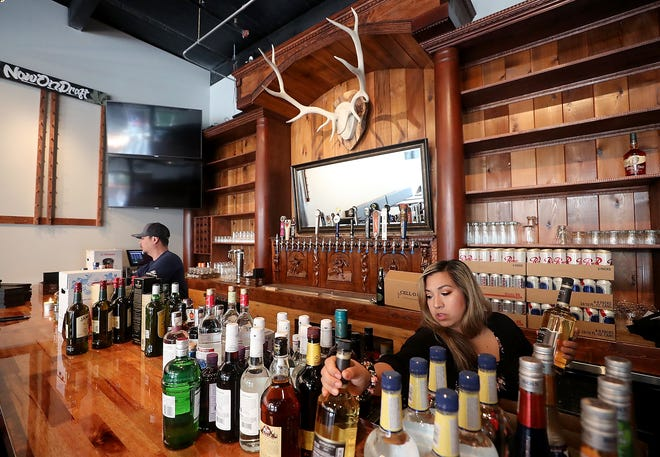 Bartender Raquel Hamilton, right, unpacks bottles of liquor to place on the shelves behind the bar to prepare for the opening of Axe & Arrow Gastropub in Bremerton.
