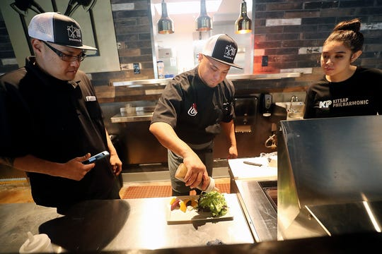 Axe & Arrow Gastropub chef Adam Tabura, center, puts the finishing touches on confit beet salad as he trains kitchen staff members Charles Farfan, left, and Ericka McDonald, right, at the soon to open downtown Bremerton restaurant on Wednesday.