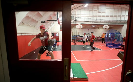 Crosspoint's Bryce Baird is framed in the gym door as he practices his pitches on Tuesday, May 14, 2019.