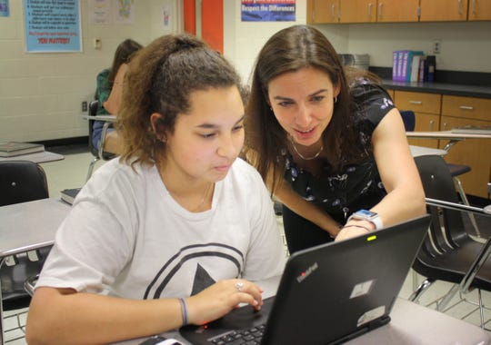 Vanessa Price helps one of her students at Spruce Creek High School in Port Orange during lunch. She worked in Brevard County, where she was a Teacher of the Year finalist, for five years before leaving for Volusia County.