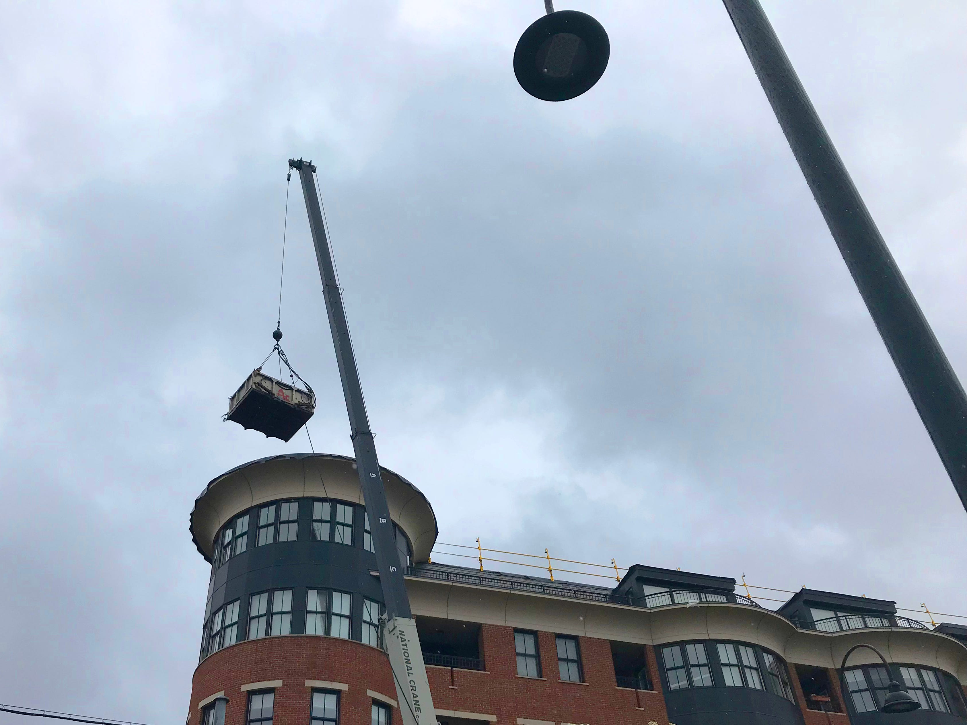 A crane operated by Williston-based A.C. Hathorne Roofing Contractor hauls construction debris down from a roof at Battery and College streets in Burlington on Tuesday, May 14, 2019.