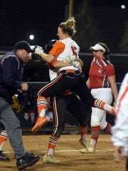 Zoiee Smith is hugged by teammate Kenzie Penrod after driving in the game-winning run in a Division II district semifinal against Logan Elm on Tuesday in Athens. The Tigers prevailed, 2-1, in eight innings.