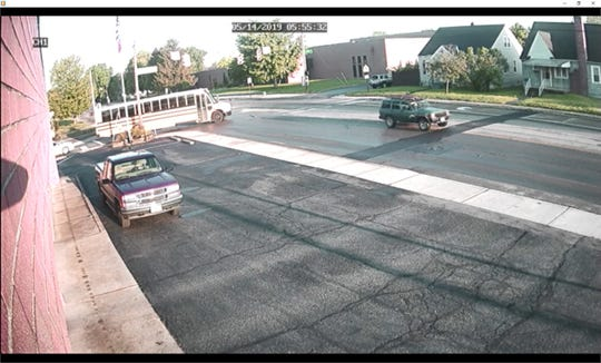A surveillance video image shows a green Jeep Cherokee with wood on top Chillicothe police say struck a Chillicothe City Schools bus after running a red light on East Main Street at Douglas Avenue on Tuesday morning.