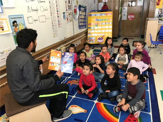 A father reads to his child's Head Start class at Grant Early Learning Center as part of a Supermen Read initiative to highlight male role models.