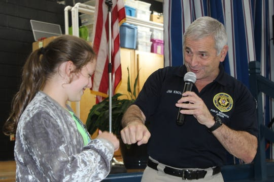 Hailie Latham, a 10-year old fourth grader at Moore Magnet Elementary, shares a fist bump with Clarksville Police spokesperson Jim Knoll while being honored for heroism on May 15, 2019.