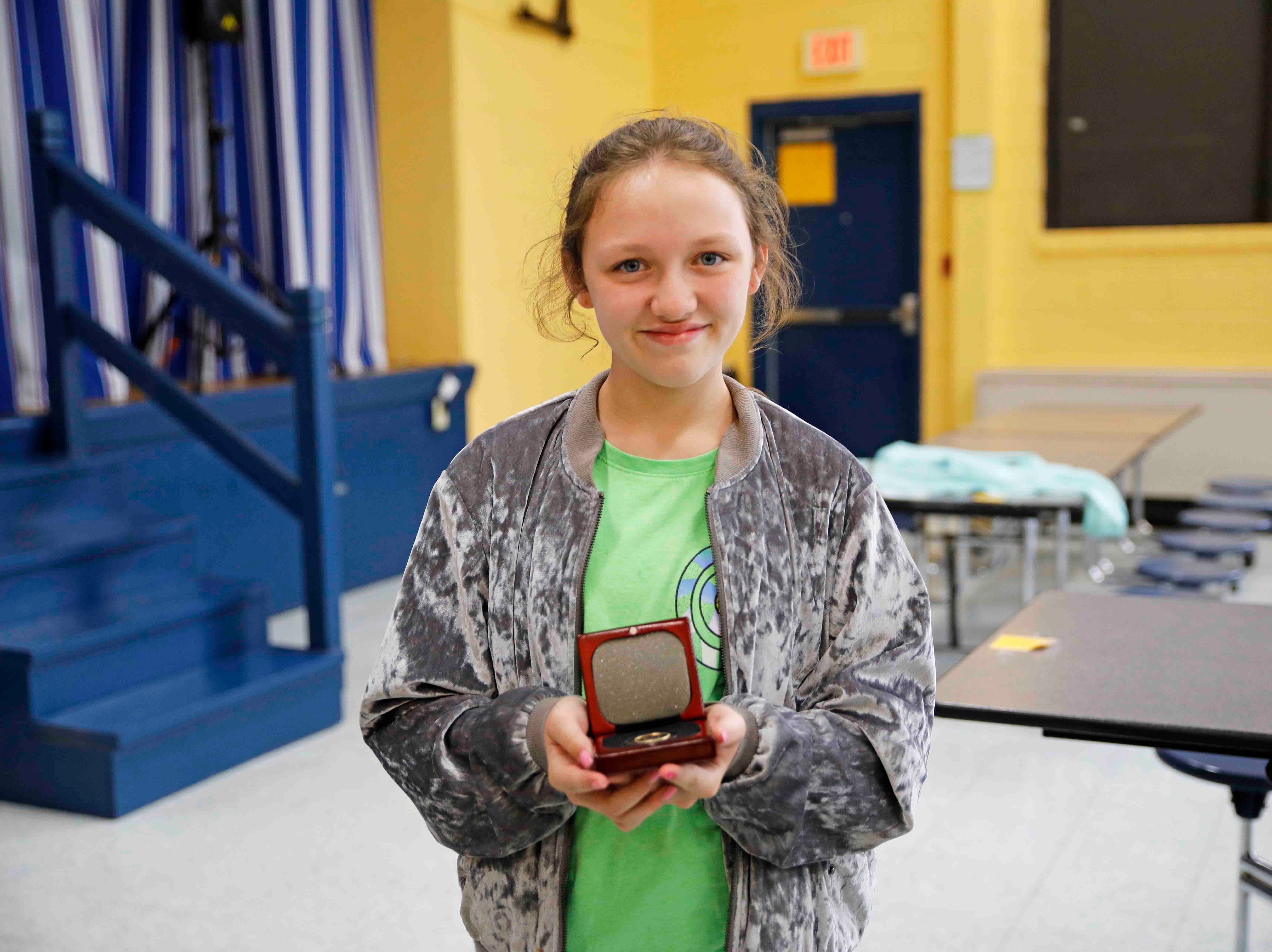 Hailie Latham, a 10-year old fourth grader at Moore Magnet Elementary, shows off her award after Clarksville Police honored her for heroism during a ceremony on May 15, 2019.