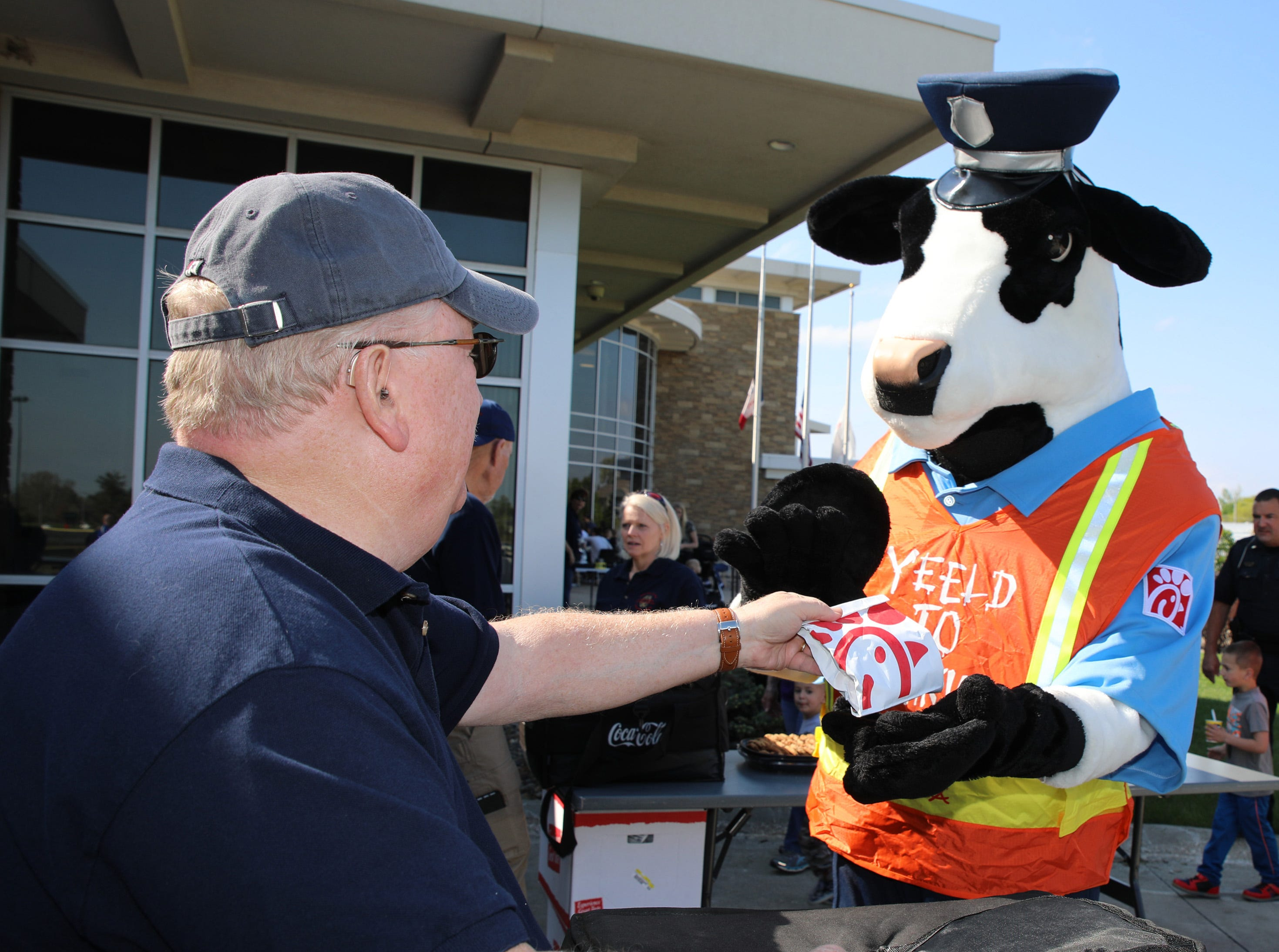 The cow from Chick Fil-A receives a free sandwich from Jerry Swanberg of the Ankeny Citizen's Police Academy during the Ankeny Police Week Community Picnic on Tuesday, May 14, 2019 at the Ankeny Police Headquarters located at 411 SW Ordnance Road. The event featured a tour of the police station, magician Jonathon May, free Chick Fil-A sandwiches for the first 1,000 guests, free Kona Ice, temporary tattoos, and a great opportunity to meet the officers who protect and serve the city of Ankeny.