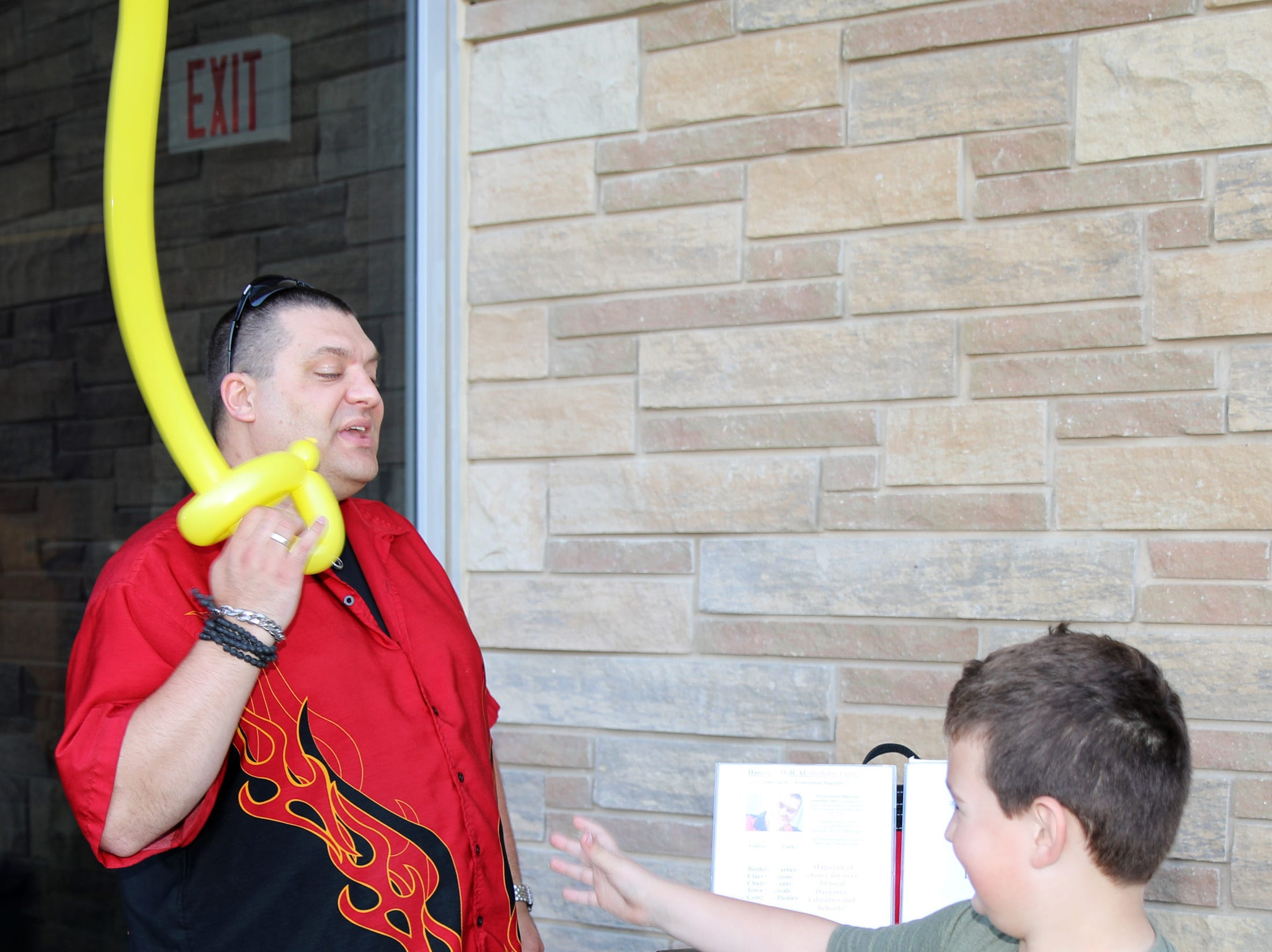 Professional Magician Jonathan May prepares to hand ower the balloon sword to William Barlow, 8, of Ankeny during the Ankeny Police Week Community Picnic on Tuesday, May 14, 2019 at the Ankeny Police Headquarters located at 411 SW Ordnance Road. The event featured a tour of the police station, magician Jonathon May, free Chick Fil-A sandwiches for the first 1,000 guests, free Kona Ice, temporary tattoos, and a great opportunity to meet the officers who protect and serve the city of Ankeny.